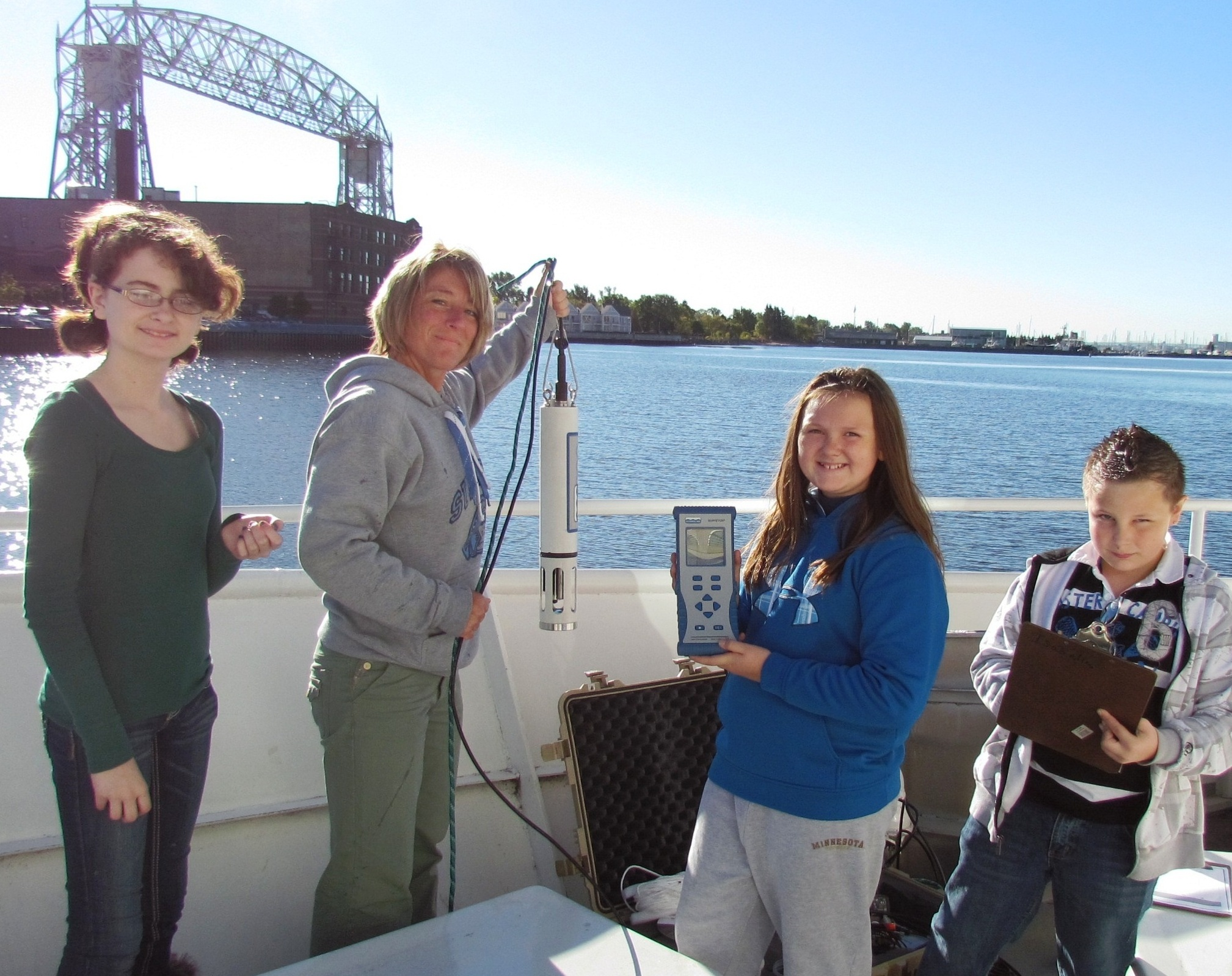 From left: a female student, a female teacher holding a Hydrolab DS5 measurement tool, a female student holding a different Hydrolab DS5 measurement tool, and a male student holding a clipboard stand on a boat.