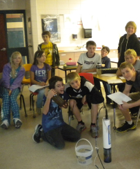 Ten students pose for a picture in their classroom, sitting at their desks or on the floor. The Limno Loan water sampling tool sits on the floor at the front center of the picture.