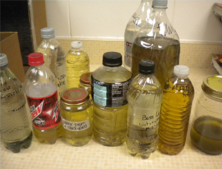 Ten plastic bottles of various types containing water samples, which vary in color from clear, to yellow, to brown.